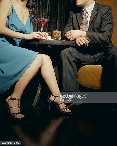 young couple at table in lounge, mid section - low section stock pictures, royalty-free photos & images