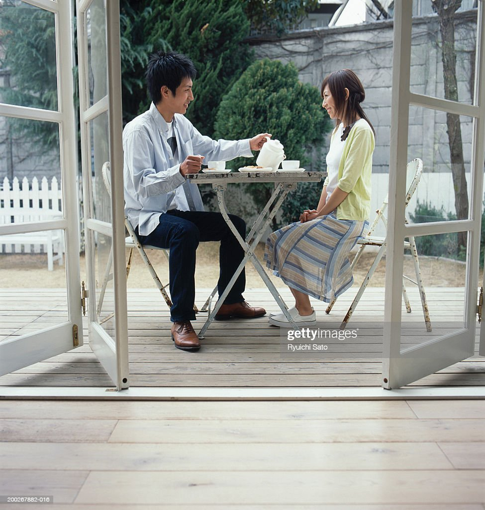 Young Couple At Table Outdoors Man Pouring Tea View Through Open