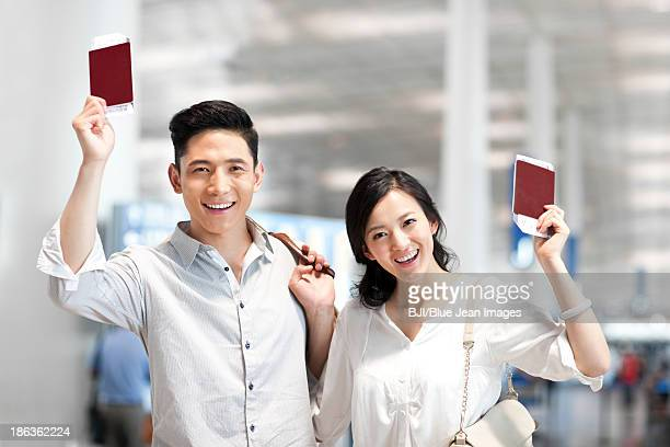 Young couple at the airport with flight tickets and passports