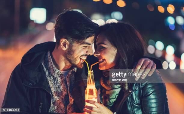 young couple at the bridge drinking cider from one bottle with drinking straw - love you stock photos and pictures