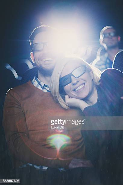 Young couple at the cinema watching movie