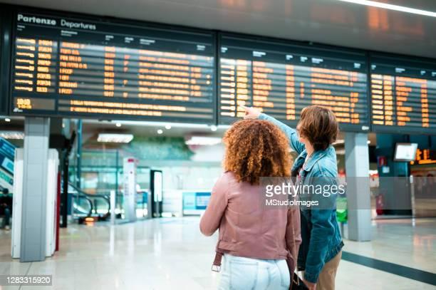 junges paar an der u-bahn-station mit blick auf die informationstafel - anzeigetafel stock-fotos und bilder