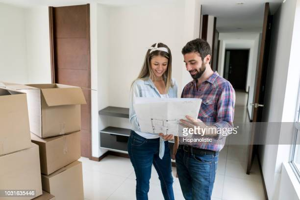 young couple at their new home looking at a blueprint and planning how to arrange the things in the boxes - hispanolistic stock photos and pictures