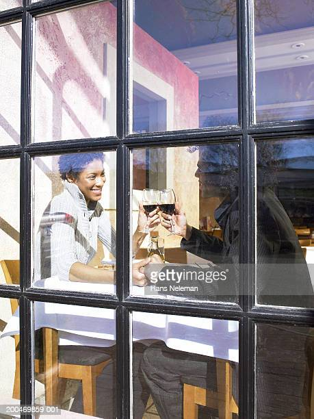 Young couple at window table in restaurant toasting with red wine