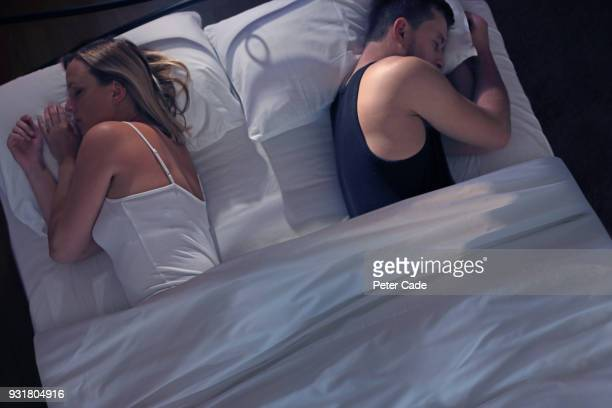 young couple back to back in bed - beautiful people stock pictures, royalty-free photos & images