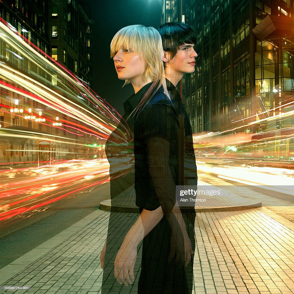 Young couple back to back in street, night (Digital Composite) : Stock Photo