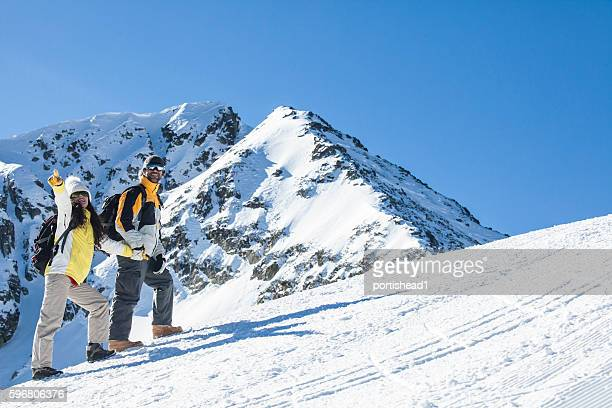 Young couple backpackers climbing on snow mountain