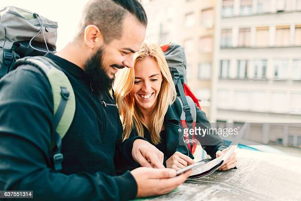 Young Couple Backpackers Looking At Map In The City