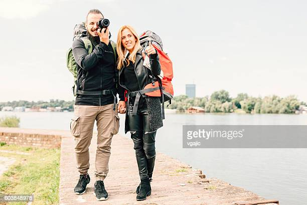 Young Couple Backpackers Standing On Brick Wall And Photographing.