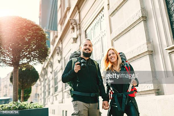 Young Couple Backpackers Walking In The City.