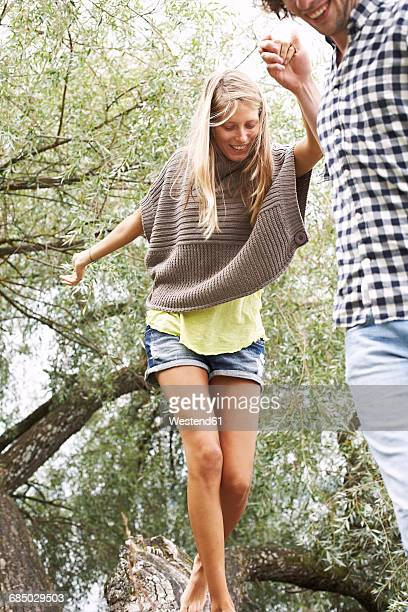 Young couple balancing on a tree trunk