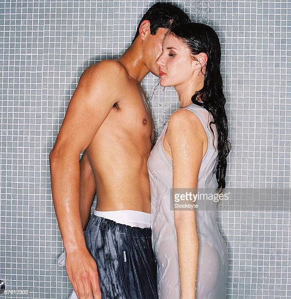 young couple bathing together - couple and kiss and bathroom stock photos and pictures
