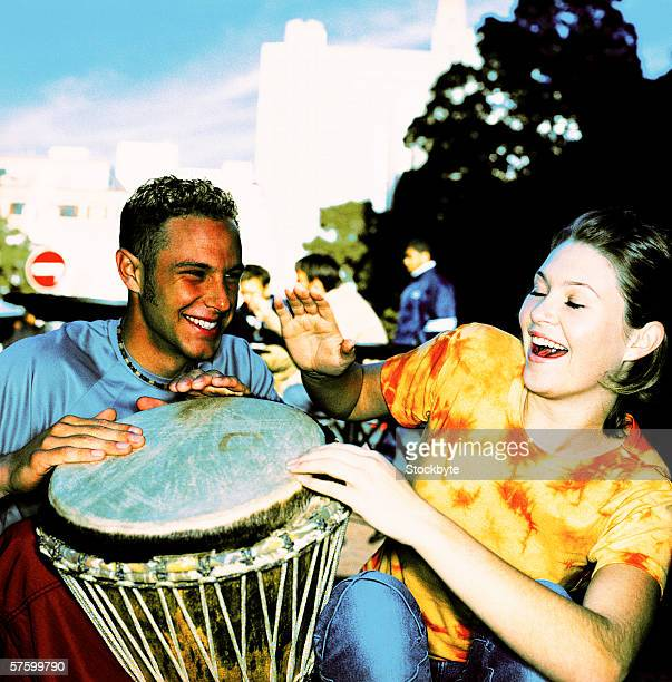 Young couple beating a drum with people in the background