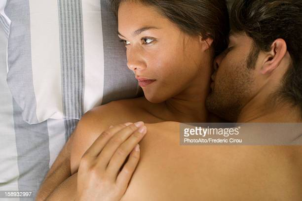young couple being intimate in bed, woman looking away - novio relación humana fotografías e imágenes de stock
