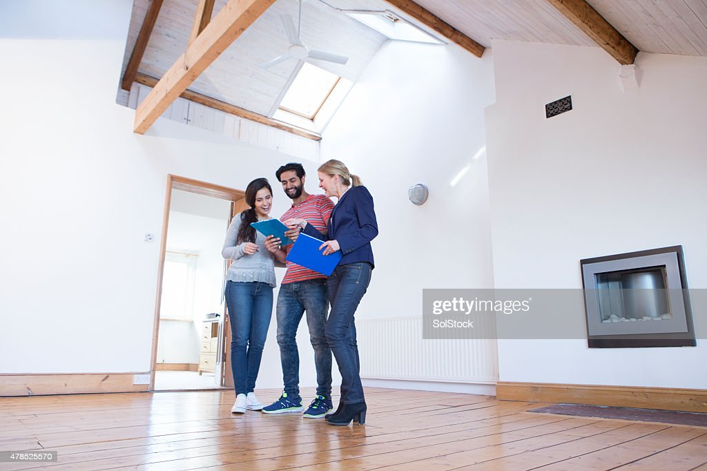 Young Couple Being Shown a New Home : Stock Photo