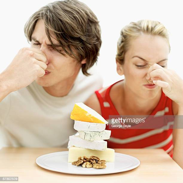 Young couple blocking their noses over a plate of assorted cheeses