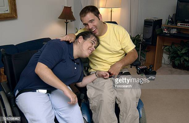 a young couple, both with disabilities, hugging, holding hands with each other and enjoying being together. - cerebrum stock pictures, royalty-free photos & images