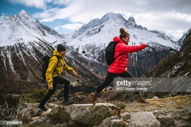 young couple bound along rocky ridge in the mountains - 25 29 anos imagens e fotografias de stock