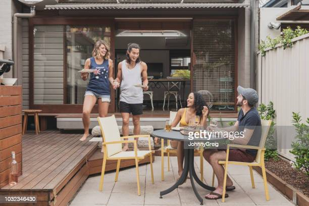 young couple bringing food out to two friends sitting on patio - arrival stock pictures, royalty-free photos & images