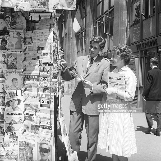 A young couple browse a magazine stand in Paris June 1960