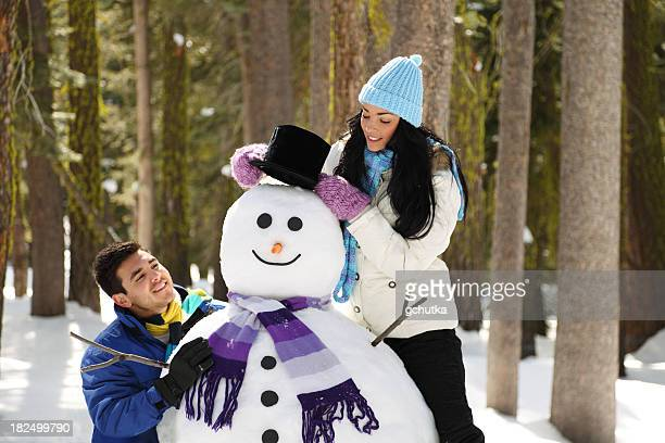 young couple building a snowman - gchutka stock pictures, royalty-free photos & images