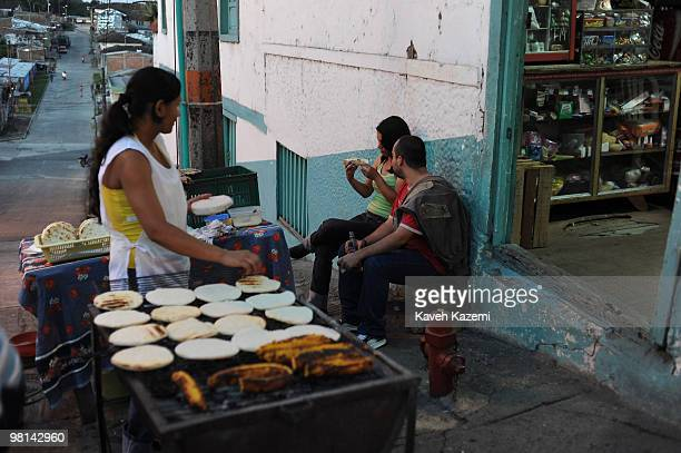 A young couple buy Arepa from a street vendor on the main street in the city center An arepa is a bread made of corn popular in both Colombia and...