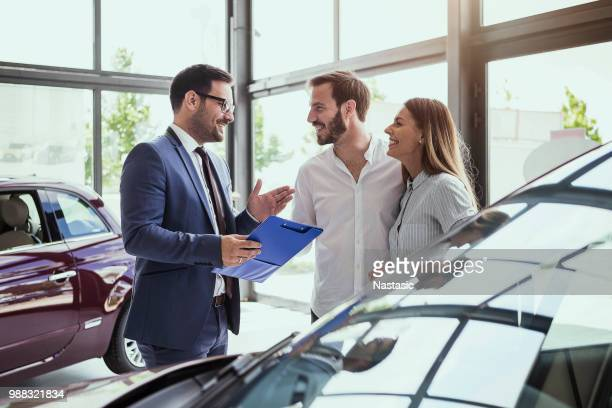 young couple buying a car - showroom stock pictures, royalty-free photos & images