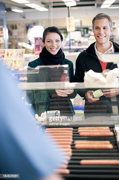 Young couple buying food at gas station