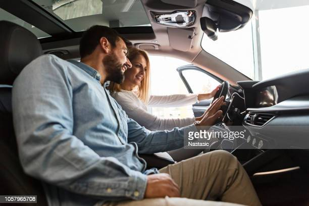 young couple buying new car - car dealership stock pictures, royalty-free photos & images