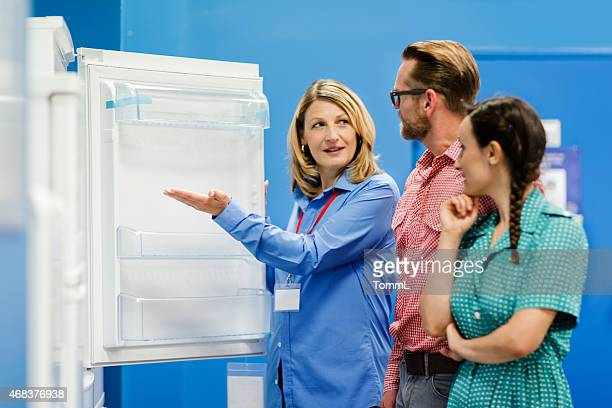 young couple buying refrigerator in appliance store - electronics store stock photos and pictures