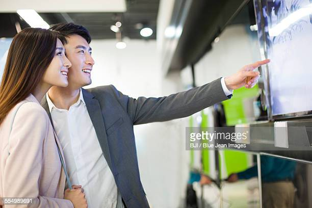 Young couple buying television in electronics store
