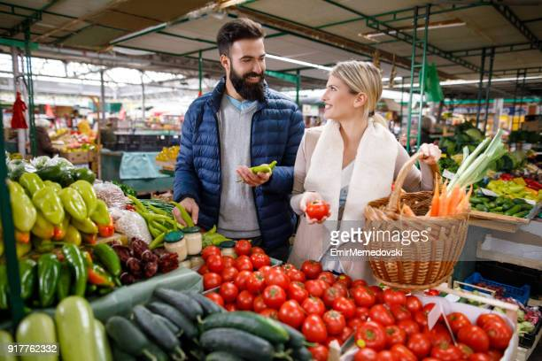 young couple buying vegetables at farmer's food market stall - farmers market stock pictures, royalty-free photos & images