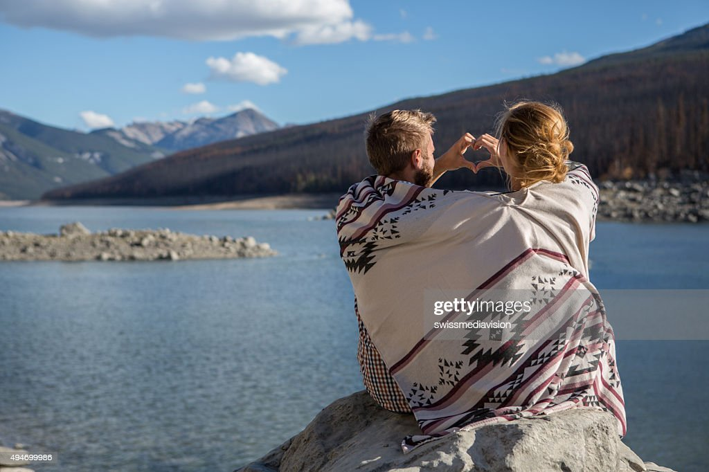 Young couple by the lake making heart shape with hands : Stock Photo