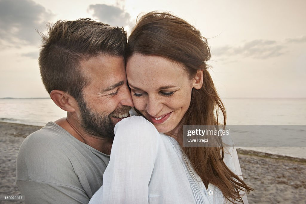 Young couple by the sea, smiling : Stock Photo