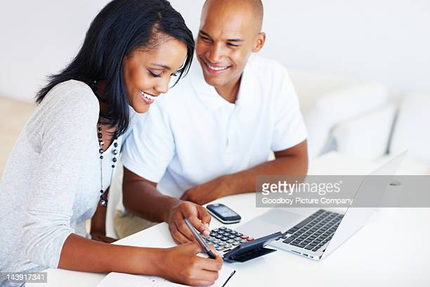 Young couple calculating monthly expenses