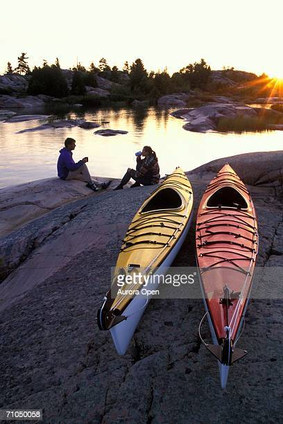 young couple camped on shore of georgian bay with sea kayaks, lake huron, ontario, canada. - sudbury canada stock photos and pictures