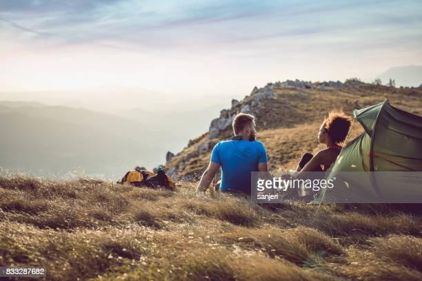 pareja joven acampar en la cima de la colina - camping fotografías e imágenes de stock