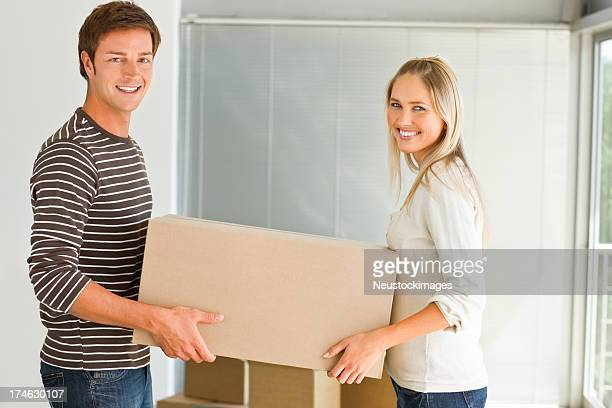Young couple carrying a cardboard box