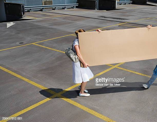 young couple carrying box on rooftop carpark, elevated view - carrying stock pictures, royalty-free photos & images