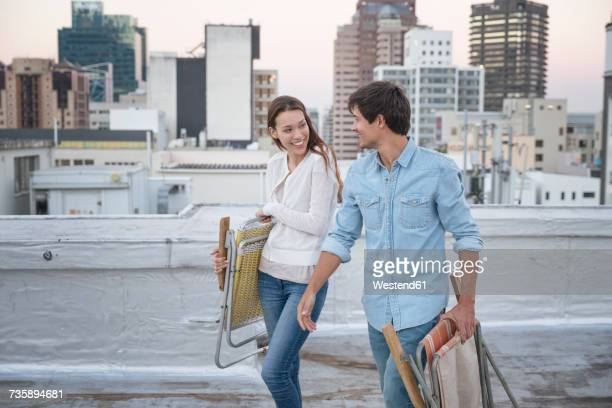 young couple carrying folding chairs on a rooftop terrace - cadeira dobrável - fotografias e filmes do acervo