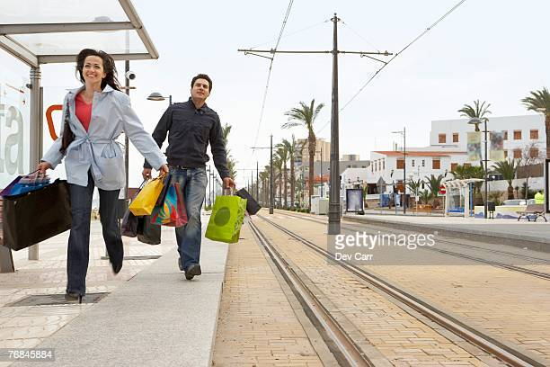 Young couple carrying shopping running to tram stop