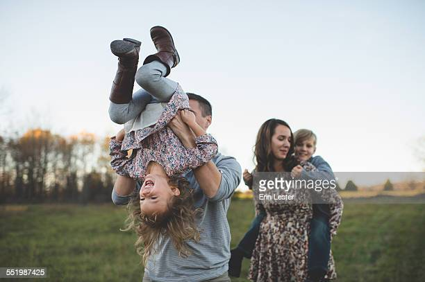 young couple carrying son and daughter in field - family with two children stock photos and pictures