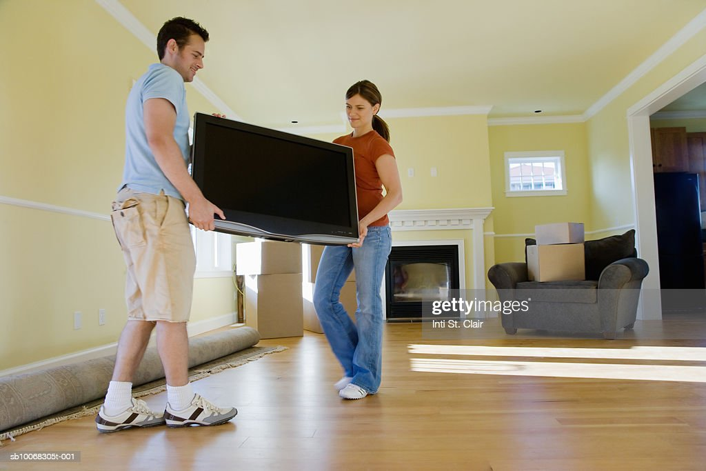 Young Couple Carrying Television In Living Room Of New Home Stock Photo