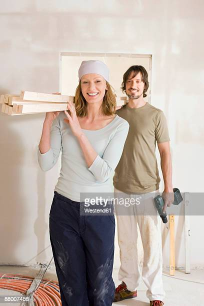 Couple carrying wooden planks at home, portrait