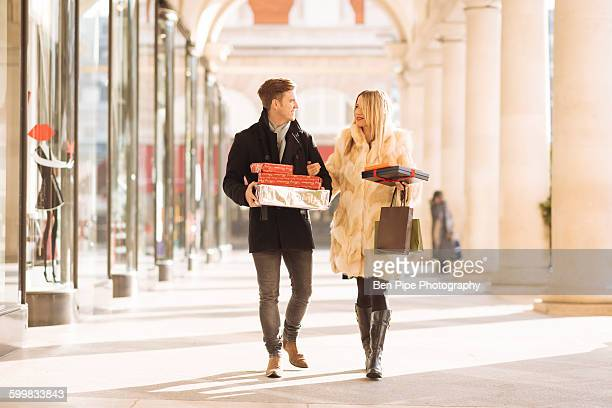 Young couple carrying xmas gifts strolling in Covent Garden, London, UK