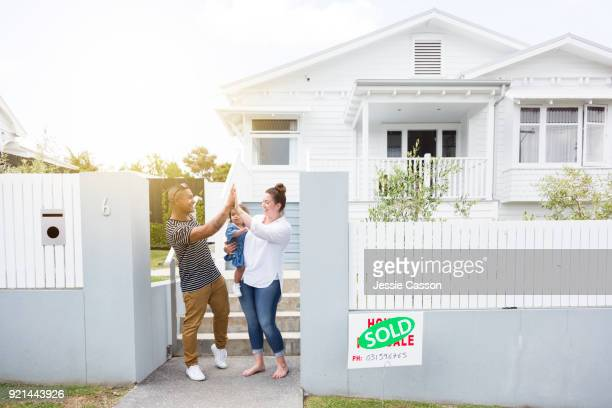 Young couple celebrate in front of their new home