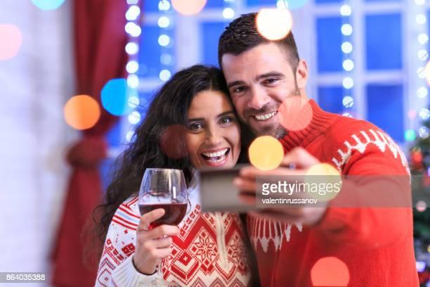 Junges Paar feiert Weihnachten zu Hause und Maing selfie