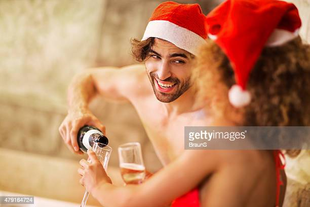Young couple celebrating Christmas in jacuzzi and enjoying in champagne.