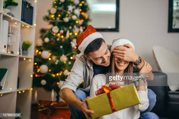 young couple celebrating christmas - exchanging stock pictures, royalty-free photos & images