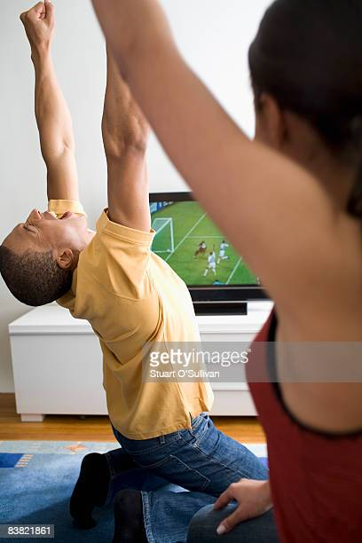 Young couple celebrating in front of television